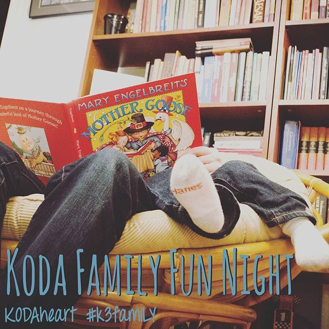 """[Image Description: """"KODA Family Fun Night"""" is written in a dark teal color in the very bottom of the photo. The photograph is of a adult and child's legs sitting in a large bowl like wood chair. They are reading """"Mary Engelbreit's Mother Goose"""". Behind them sits a full bookshelf. """"KODAheart #k3family"""" in a dark teal color underneath """"KODA Family Fun Night"""" in the bottom left corner.]"""