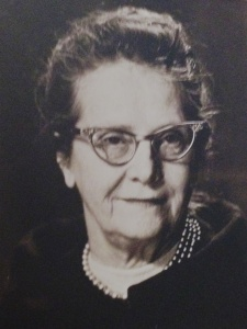 This black and white portrait of Elizabeth Benson shows a white woman with 1960's-style-horn-rimmed glasses and pearl necklace smiling at the camera. Her dark hair is pulled back atop her head and a broad collar encircles her shoulders.