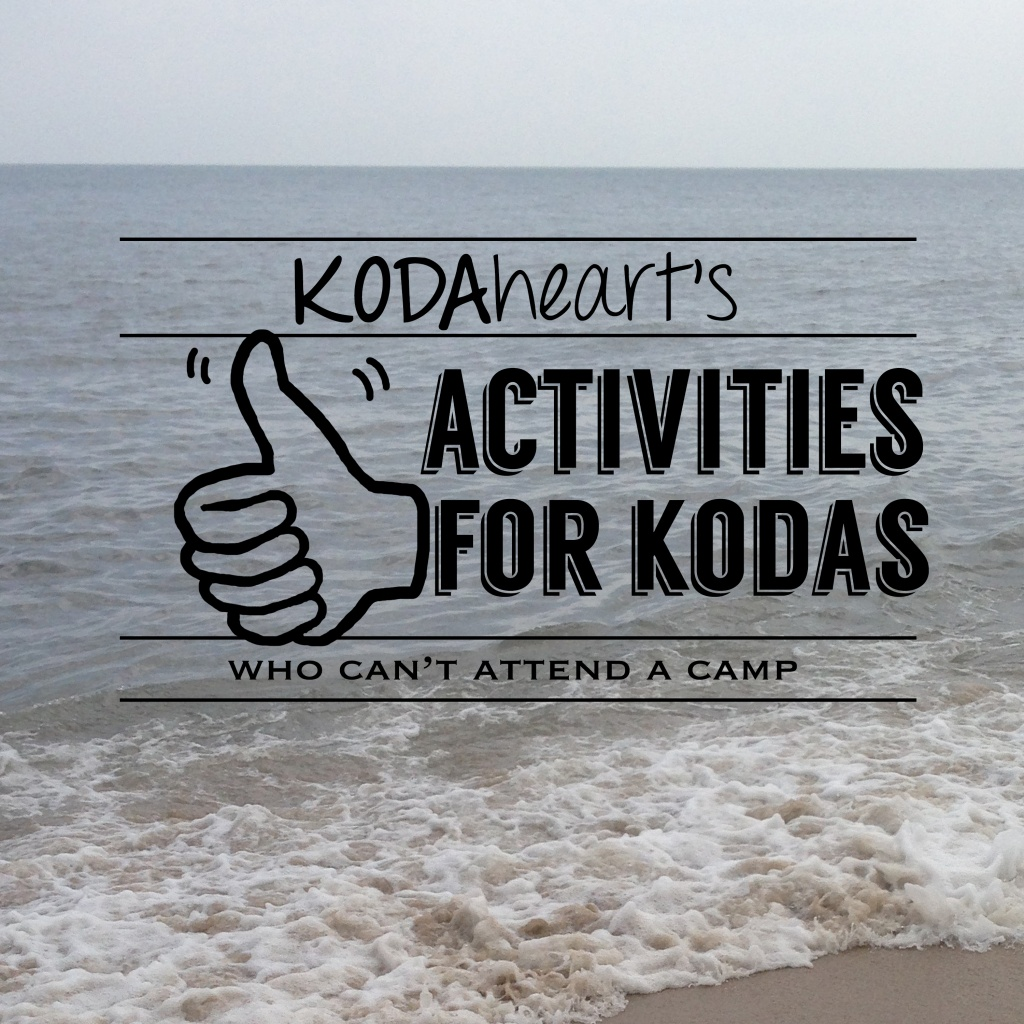 """[Image Description: A thumb, outlined in black, signs """"10"""" with accompanying text that reads: """"KODAheart's [10] Activities for kodas who can't attend a camp"""". In the background is a picture of the ocean, with a wave gently crashing on the beach.]"""