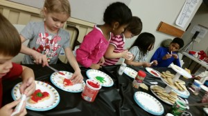 A group of kids sit around a table draped with a black table cloth. In the center of the table is a three tiered cookie stand with stacks of unfrosted cookies. In the middle of the table are different colors of frosting, frosting tubes, sprinkles containers, and empty paper plates. Around the table kids bend over paper plates, adding green and red frosting, and multi-color sprinkles to 'I-Love-You' hand-shaped cookies.