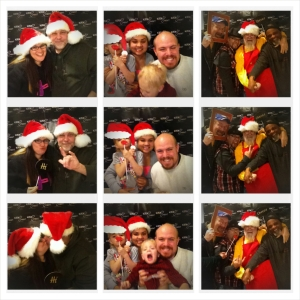 """[Image Description: A collection of three photostrip images. Each photostrip has three small, square images. In the first photo of the first photostrip, a man and woman wearing red and white Santa hats smile into the camera. In the second photo, she holds up a black cardboard speech bubble that reads, 'hi' and he signs 'I-Love-You'. In the third photo, the two kiss as she holds up the sign. In the second photostrip, a man, woman and two young children take a group photo. On the left, the young girl, in a grey t-shirt, holds a red cardboard pair of lips and a red and white cardboard Santa hat. Next to her, a woman wears a red and white Santa hat. On the right, a man lifts a young boy in a red shirt. In the first photo, the group smiles for the camera, the young boy moving out of frame. In the second photo, the family laughs and the young boy is not pictured. In the third photo the group smiles, and the boy opens his mouth widely. In the third photostrip, a group of four men crowd into the frame. On the left, a man in a blue sweatshirt and blue baseball cap holds a green and white cardboard frame. Next to him holding a black cardboard sign that reads, 'cheese', a man in a black fedora and red and black plaid shirt has an arm around the third man, wearing a yellow shirt and a red Santa apron with fake yellow buttons and a black belt. He has a full white beard and a red and white Santa hat. On the far right, stands a man with a black backwards baseball cap and black shirt. In the photos, the men smile and make faces, with their arms around their shoulders. In the third photo an arm appears from off camera holding a pair of cardboard red lips to the mouth of the man in the fedora. In each photostrip, the group stands in front of a black background with the KODAheart logo printed in white. It reads """"KODAheart, Two Worlds, One Family"""". The KODAheart logo is a slanted infinity symbol, with the top right circle replaced by a heart. The word KODA in all capital letters to the"""