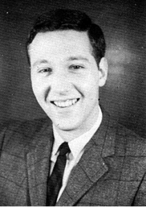 A young white man in a plaid suit jacket and dark tie, smiles pleasantly at the camera.