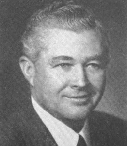 A black and white image of a white man with a suit and tie, smiling at the camera.