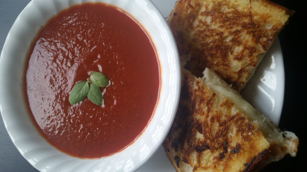 [Image Description: A white plate has a bowl containing tomato soup with three basil leaves floating on the top to the right of a grilled cheese sandwich cut in half.]