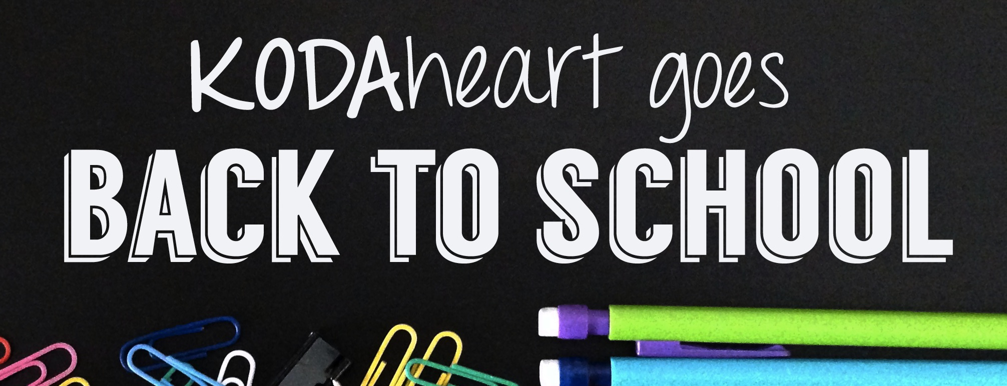 "White text hovers over colorful school supplies, including paper clips and mechanical pencils. The text reads: ""KODAheart goes Back to School"""