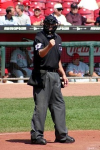 Image Description: An umpire shows the strike symbol dressed in uniform. He stands in front of a baseball dugout.