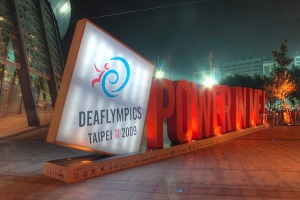 "[Image Description: A large illuminated sign ""Deaflympics, Taipei 2009"" in a white box, to the right red letters spell out ""Power in me!"" Is placed in front of illuminated buildings.]"