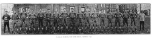Image description: A row of 18 males are lined up side by side dressed dark colored in uniforms with their hands behind their backs in front of a brick building.