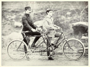 Image Description: Two white males are holding onto a two person bicycle, front male is wearing a white uniform, while the male in the back is wearing a black uniform. Both have one leg up on the bike.]