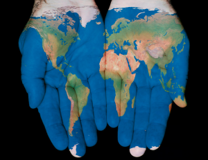 """[Image Description: Two hands side by side palms up with an image of the world and its continents and oceans """"painted"""" on.]"""