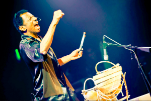 [Image Description: An African American male stands with his mouth open/singing in front of a musical instrument and a microphone on a stand with his fist pumped in the air and drumsticks in his other hand.}