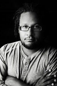 [Image description: A black and white image of an African American man with chin-length dreads, looks into the camera with his arms crossed across his chest. He is wearing dark-rimmed glasses and a three-button shirt.]