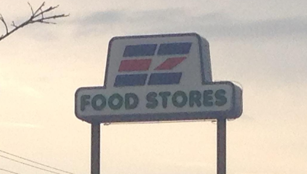 """[Image Description : A sign that reads """"Food Stores"""" rests high up with an illuminated sunset and few clouds. In the background some telephone poles line the bottom quarter of the photo.]"""