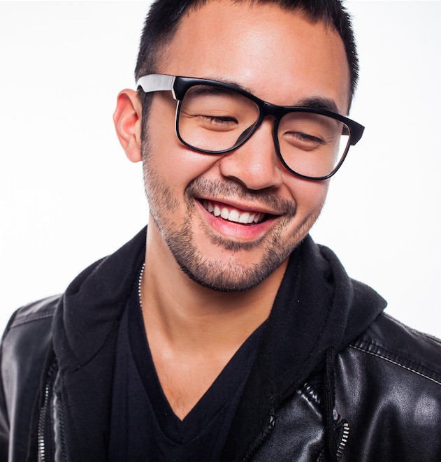 [Image description: a Taiwanese man, smiling, with black rimmed glasses looking to the lower right wearing a leather jacket.]