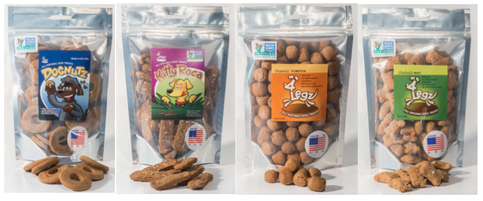 """[Image description: Four bags of pet treats in ziplocked bags with see through front covers are lined up side by side Each one with a different name and different shape. The labels from left to right read Dognuts, Kity Roca, Organic pumpkin, and Chehalis Mint. All of the bags have an american flag sticker on the lower right corner with the words """"made in america"""".]"""