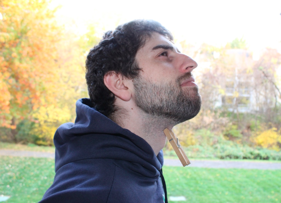 [Image description: A man is standing with their head cocked upward. He is wearing a blue hoodie and on his neck a clothes pin is pinched on his throat. Behind him, trees with fall leaves are visible.]