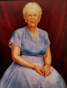 Image description: This painted portrait shows Elizabeth Peet seated with her hands clasped in her lap. She is wearing a belted blue dress and a long necklace. Her white hair is pulled back and she looks out from the painting with a calm smile.