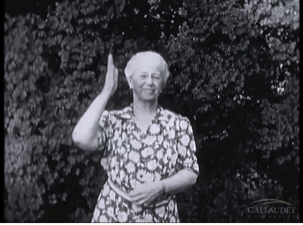 [Image Description: This is a screenshot of a black and white video. A white woman, with grey hair is signing with a small smile on her face.]