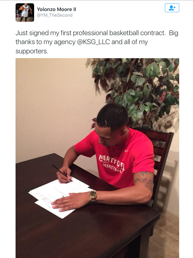 "Image Description: A screenshot of a tweet, featuring black text that reads ""Just signed my first professional basketball contract. Big thanks to my agency @KSG_LLC and all of my supporters."" The tweet includes a large image of a man wearing a red shirt bent over a stack of white papers, holding a pen.]"