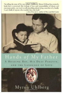 """Image Description: The title is in light teal banner placed just below the center of the book """"Hands of My Father"""". Behind this banner is a photo in a sepia tone of a man with a child in their lap looking at a book. Above the photo is a review, below the title is a picture of a photo of a couple with a silver border."""