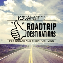"[Image Description: A thumb, outlined in black, signs ""10"" with accompanying text that reads: ""KODAheart's [10] Road Trip Destinations for KODAs and their families. In the background, an open highway trailing off into the distance with a cloud filled blue sky overhead.]"