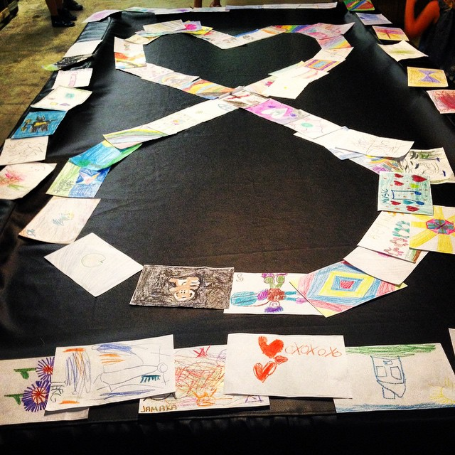 [Image description: Childrens' drawings are covering a large black table, in the center they are formed into the shape of the KODAheart infinity logo.]