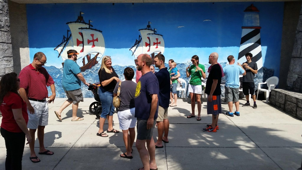 [Image description: A group of adults in shorts and t-shirts gather in the shade, forming conversational circles in front of a large mural. Some parents are holding small children or pushing strollers. On the right, members of the KODAheart team, with green and dark grey t-shirts, can be seen engaging in conversation with groups of adults. In the background, the mural displays 2 pirate ships with red crosses on the white sails on the open water headed toward a black and white striped lighthouse with a red roof.]