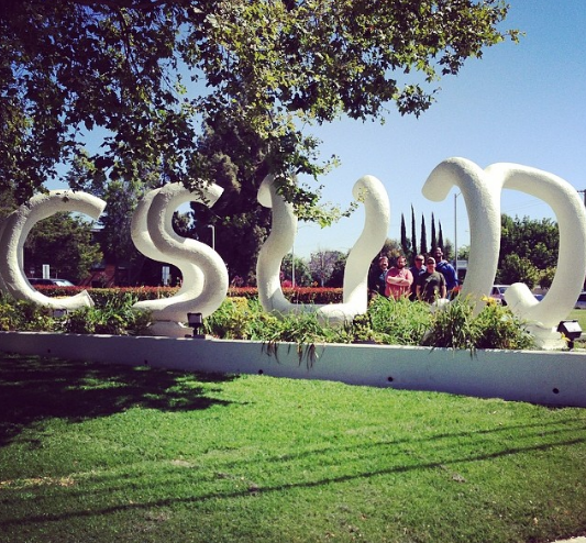 """Image description: A brightly lit photo of the """"CSUN"""" sculpture sits on a long white ledge in the grass. Behind it is a group of people, standing between the """"U"""" and """"N"""". On the top left of the photo is a over hanging tree barely touching the beginning of the sculpture."""