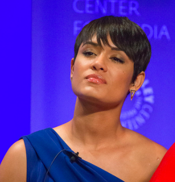 a woman with short hair stands in front of a blue background with a neutral facial expression. Her head is tilted slightly back, and she is wearing lipgloss.]