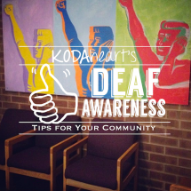 "[Image Description: A thumb, outlined in black, signs ""10"" with accompanying text that reads: ""KODAheart's [10] Deaf Awareness Tips For Your Community"" In the background, is a multi-colored pop-art style painting. The painting depicts a person holding a hand over the left ear, with the right hand raised in a fist.]"