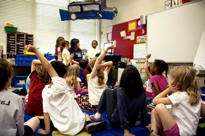 [Image description: A group of children are seated on the floor of a classroom. In the foreground, children are raising hands, with their back to the camera, facing the front of the room. In the background, a child stands holding a book.]