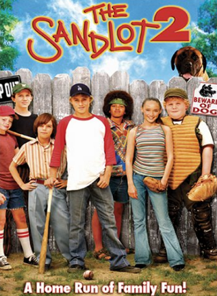 """[Image description: Movie cover for Sandlot 2. Red text against a blue sky reads, """"Sandlot 2."""" Below, a group of children pose for a photo wearing various pieces of baseball equipment. Behind them is a tall fence with signs reading """"keep out"""" and """" beware of dog"""". Behind the fence peeks out the head of a large dog. At the bottom of the image white text reads, """"A home run of family fun!""""]"""