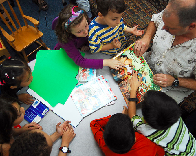 Image Description: A group of children sit huddled around a table as an adult male shows them a picture from a book. On the table there is green construction paper and other books.