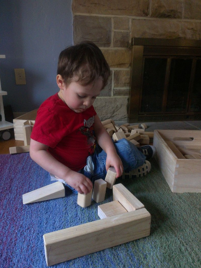 Image Description: A child wearing a red shirt and blue jeans sits in front of a fire place playing with wooden blocks