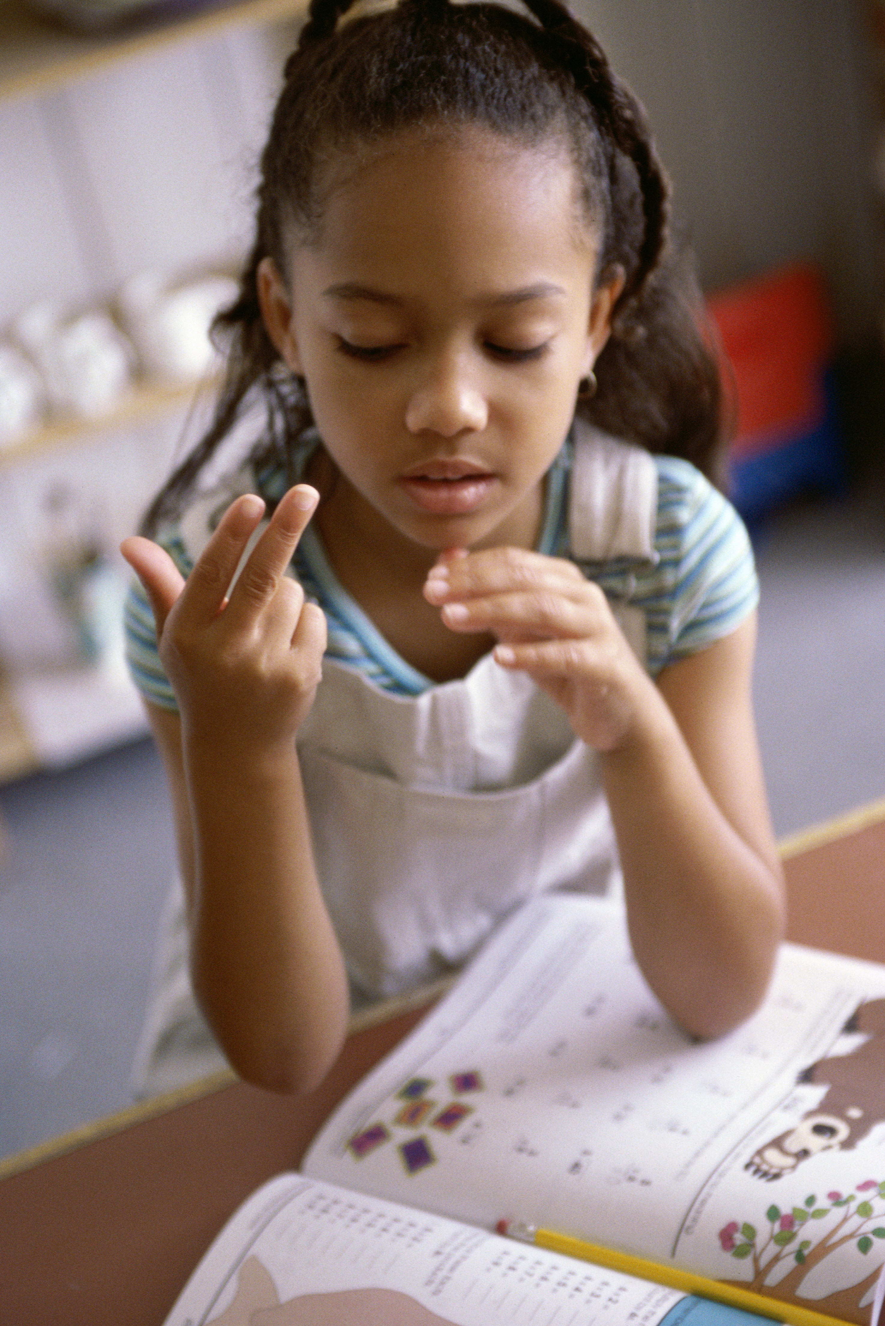 [image description: A young girl is looking down at her hands while forming the sign for 13 with her right hand.The background is blurred a bit.]