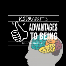 "[Image Description: A thumb, outlined in white on a black background signs ""10"" with accompanying text that reads: ""KODAheart's [10] Advantages to being Multilingual."" In the background in the bottom right corner, a grey profile of a human head with a brain colored blue orange red pink and orange highlighting the different lobes.]"