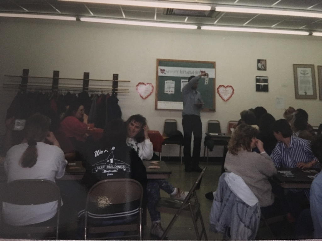 [Image description: In a open room groups of people sit around card tables, at the front of the room a person stands holding a large playing card in the air towards the crowd. There is a small chalkboard in the background.]