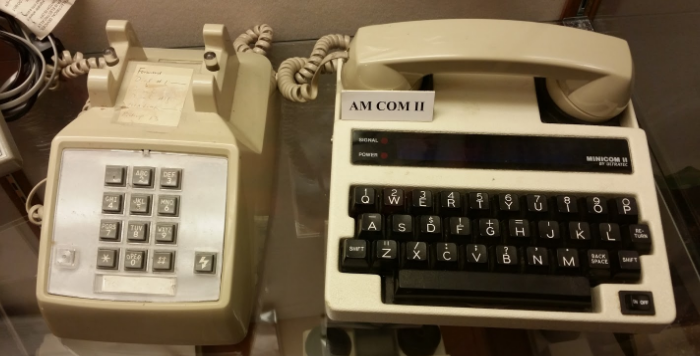 [Image Description: Photo of a beige, landline, touchtone phone with grey buttons, next to a white tty with black keys. The phone's handset placed on top of the TTY. On top of the TTY is a small white label with black letters reading AM COM II.]
