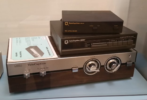[Image description: Three different versions of closed captioning devices are stacked one on top of another. The older, bigger model is on bottom with two large knobs and buttons. The two smaller, models are encased in black plastic sit on top.]