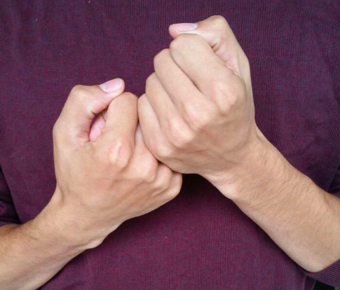 """[Image Description: A close- up image of two hands signing """"support"""" in ASL in front of a maroon background.]"""