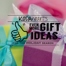 "[Image description: A thumb, outlined in black, signs ""10"" with accompanying text that reads: ""KODAheart's [10] Even more gift ideas for the holiday season."" In the background is a closeup colorfully wrapped boxes with ribbon bows.]"