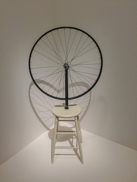 [Image description: a photograph of an art piece featuring a wooden stool with a large wheel on top.]