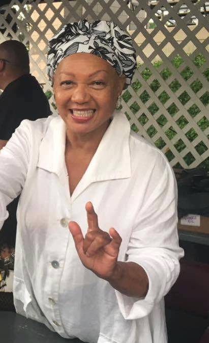 "Image Description: An African-American woman wearing a white shirt and a black and white headdress stands smiling and producing the ASL sign for ""I love you"" with her left hand."