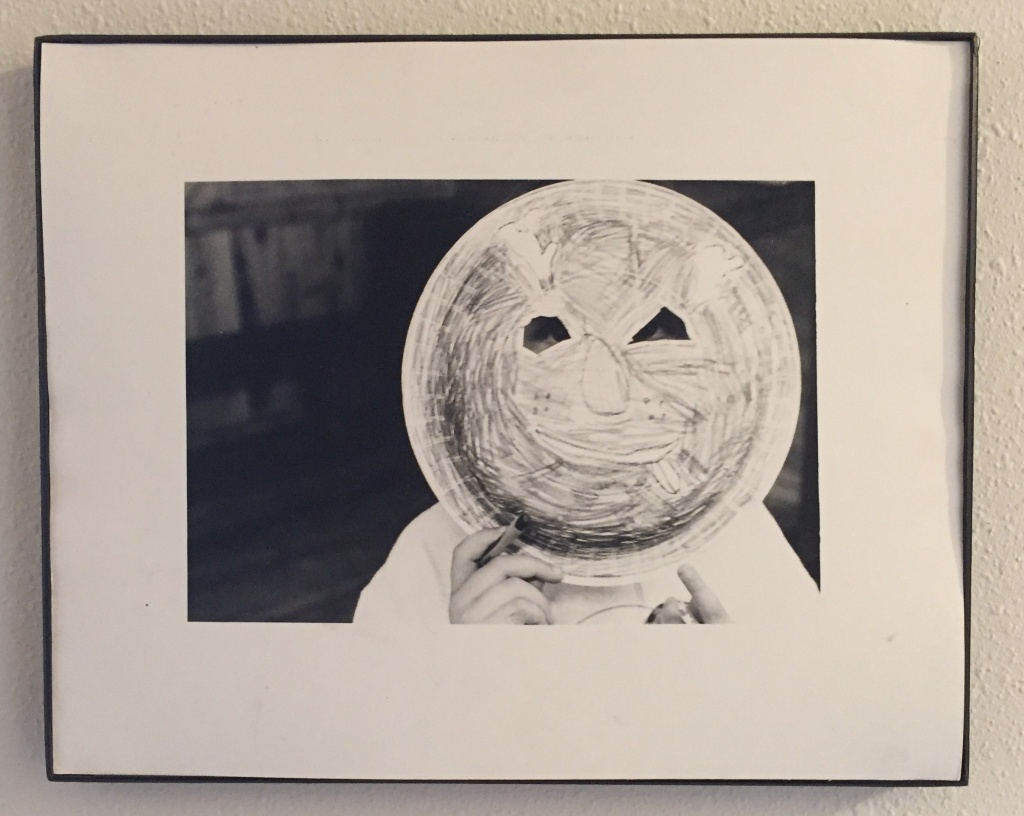 [Image description: an image of a framed black and white photograph. In the photo a child holds a paper plate mask in front of their face.]