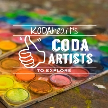 """[Image description: A photograph of two water-color palettes, smudged with vibrant colors, laying on a wooden table. Smudged dabs of color are visible on the table. Layered on top in white, is a thumb, signing """"10"""" with accompanying text that reads: """"KODAheart's [10] Coda Artists to Explore.""""]"""