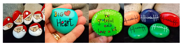 """[Image description: In the first photo is of various shaped rocks painted with a Santa Claus face. The next photo is of a turquoise painted rock with the words """"BIG Heart"""". A heart shape is between the two words. Next is a green painted rock with """"Be grateful and love alot"""" surrounded by little white dots. The void in the letters are filled in with different colors. The last photo is of orange, blue, red and green painted rocks with the word coda in the middle of a heartbeat line.]"""