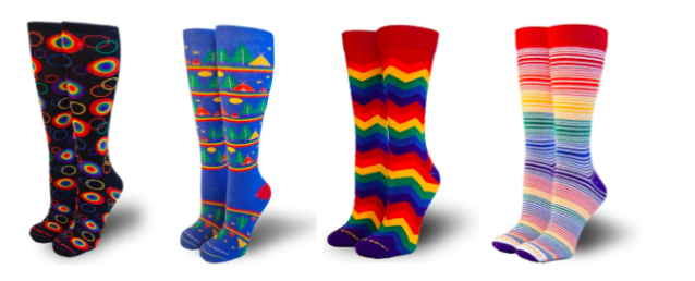 [Image description: Four pairs of colorful calf length socks are lined up. The first pair on the left side are black with primary colored circle outlines. Some of the circles are filled in with multiple rings. The second pair are blue with different campsite images with a tents and trees stacked up one on top of each other separated by a rainbow border. The next pair is a repeating primary color zigzag pattern. The last pair is horizontally striped with light and dark primary colors.]