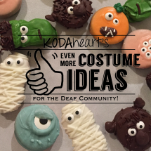 """[Image Description: A thumb, outlined in black, signs """"10"""" with accompanying text that reads: """"KODAheart's [10] Even More Costume Ideas Inspired by the Deaf Community!"""" In the background, a close-up photograph of various halloween decorated cookies including Frankenstein, werewolf, jack-o-lantern, and other various monsters.]"""