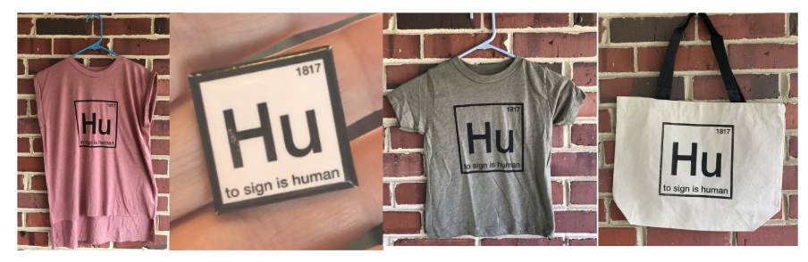 [Image description: A row of 4 different products that display the logo for To Sign is Human, in front of a brick wall. A pink sleeveless shirt with black border and lettering, a white pin with black border and lettering, a grey t-shirt with dark border and lettering, and a white tote bag with black border, lettering, and straps.]