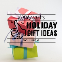 """[Image Description: A thumb, outlined in black, signs """"10"""" with accompanying text that reads: """"KODAheart's [10] Holiday Gift Ideas Volume 6"""". In the background are three square presents stacked on top of one another. The present on the bottom is wrapped in bright green wrapping and has a blue ribbon bow. On top of that is a peach colored present wrapped in a blue and white checkered ribbon. On top is a red present tied with a light purple ribbon and bow.]"""